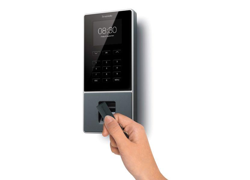 Ein RFID-Chip wird vor den Terminal eines Zeiterfassungssystems gehalten