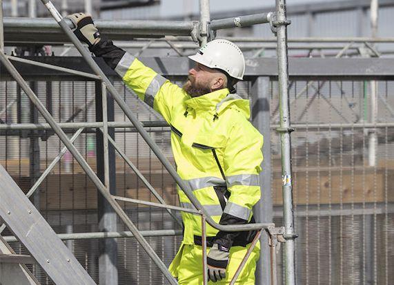 Arbeiter auf einem Gerüst mit Schutzhelm, Warnkleidung und Schutzhandschuhen