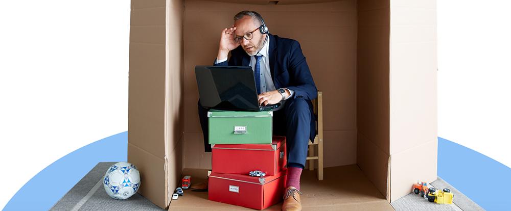 Man in maatpak zit thuis op een kleine stoel en werkt in een zeer beperkte ruimte.