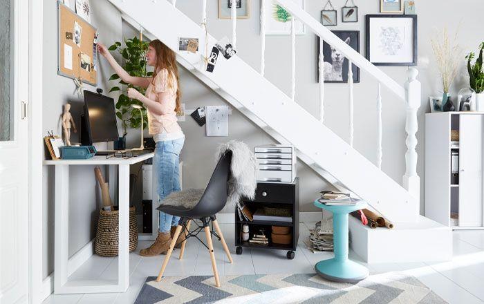 Vrouw werkt in een thuiskantoor in een kleine kamer met bureau, krukje en verrijdbaar ladeblok
