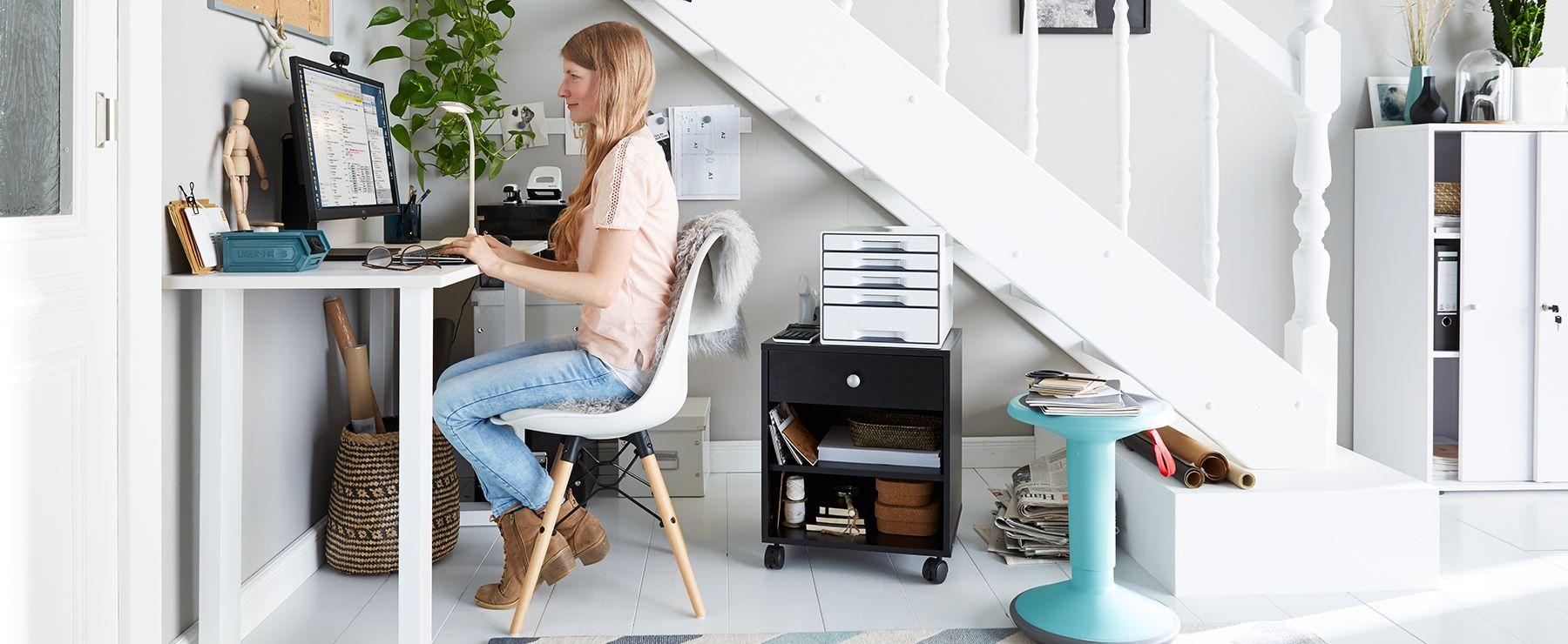 Frau arbeitet im Homeoffice in einem kleinen Raum mit Schreibtisch, Hocker und Rollcontainer