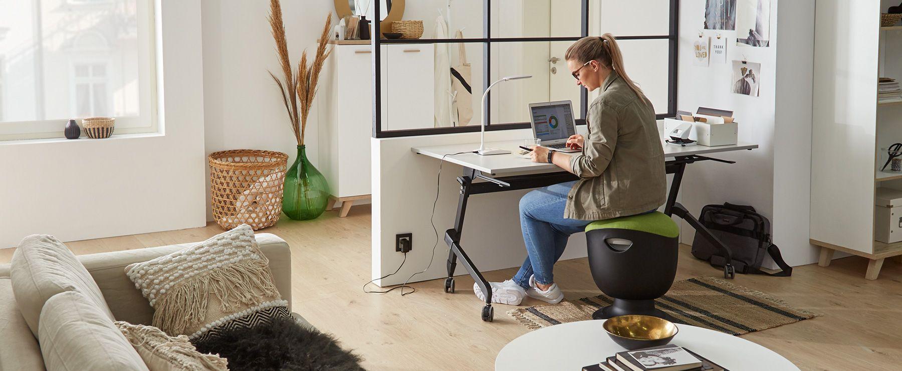 Frau arbeitet an einem klappbaren Schreibtisch im Wohnzimmer