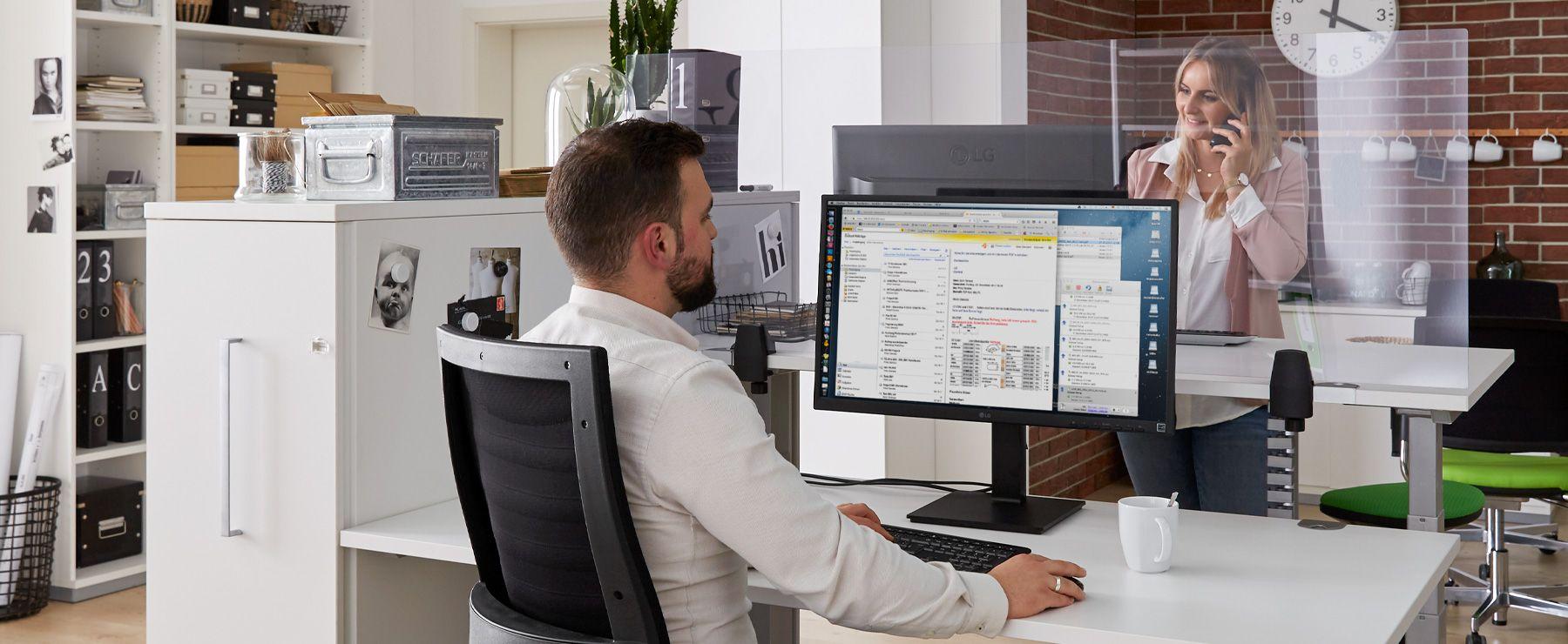 Frau und Mann arbeiten mit einer Trennwand sicher im Büro